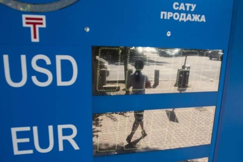 Woman walking on street is reflected on switched off electronic board in Almaty